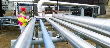Photograph of pipes leading from a storage facility being inspected.